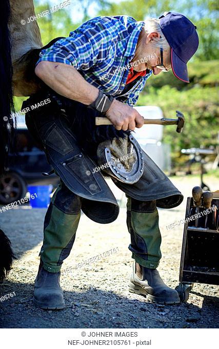 Man hammering horseshoe