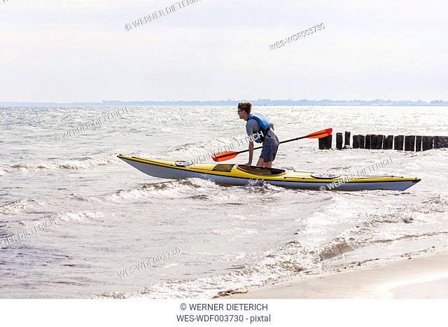 Denmark, Young man kayaking