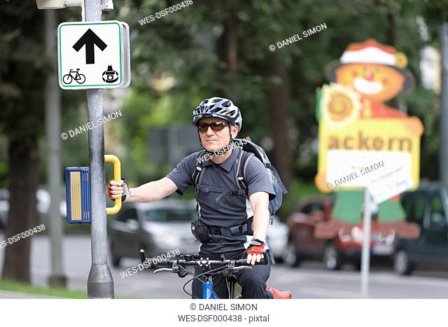 Austria, Styria, Graz, Mature man standing by road sign