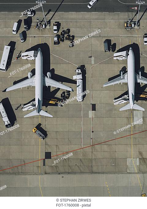View from above commercial airplanes being serviced, prepared on tarmac at airport
