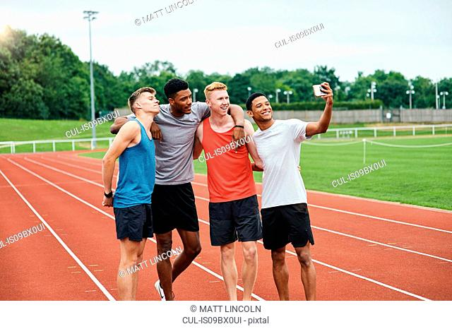 Friends taking selfie on running track