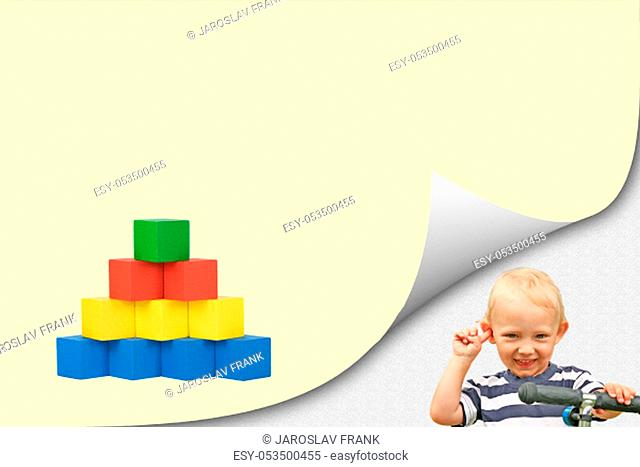 Child play with wooden toys concept. Smiling blond boy is standing in an exposed corner next to a blank yellow page with a pyramid of colorful wooden cubes...