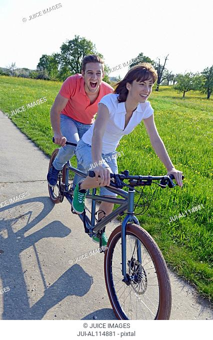 Young couple riding tandem through park