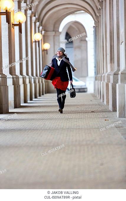 Mature woman with Christmas gift walking through city colonnade
