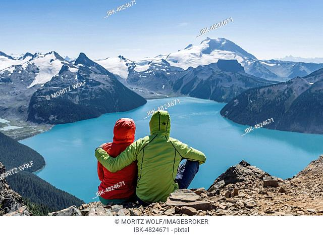 View from Panorama Ridge trail, Two hikers sitting on a rock with Garibaldi Lake, turquoise glacial lake, Guard Mountain and Deception Peak, Glacier