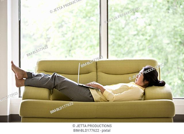 Japanese businesswoman using laptop on sofa