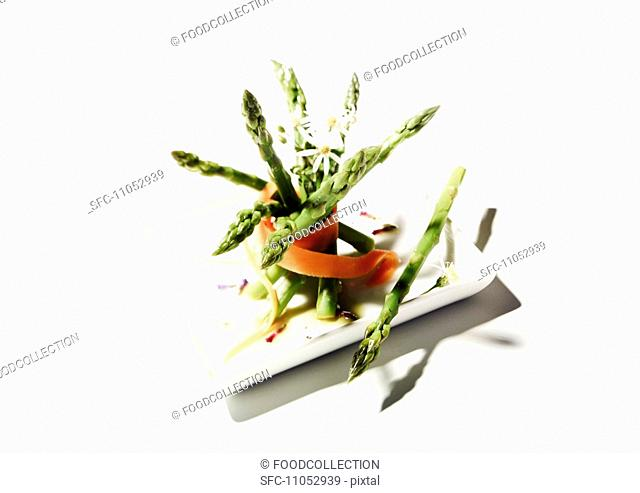 A bunch of asparagus with carrots and edible flowers