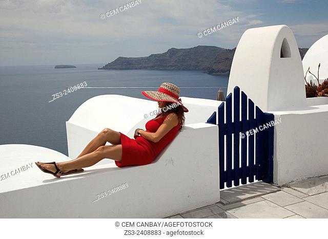 Woman in red dress sitting near a hotel entrance looking down to Caldera in Oia town, Santorini, Cyclades Islands, Greek Islands, Greece, Europe