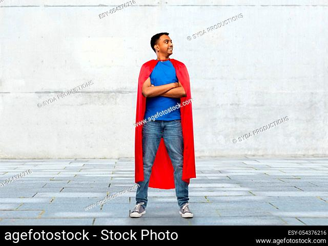 happy smiling indian man in red superhero cape
