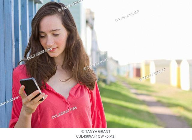 Portrait of young woman with mobile phone, Whitstable, Kent, UK