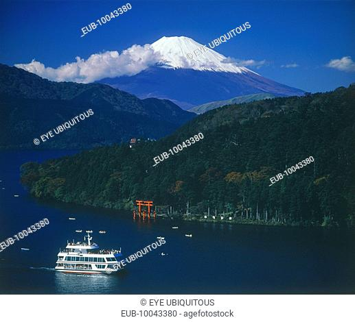 Mount Fuji with snow cap above the lake with a passenger boat passing the Hakone torii gate