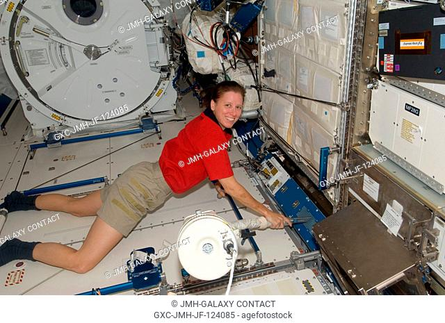 NASA astronaut Shannon Walker, Expedition 24 flight engineer, uses a vacuum cleaner during housekeeping operations in the Kibo laboratory of the International...