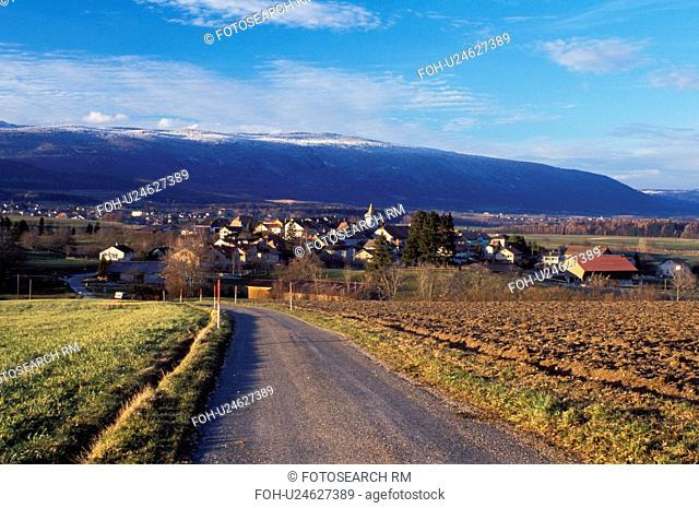 Switzerland, Vaud, Essertines-s-Rolle, Jura Mountains, Europe, A country road leads down to the village of Essertines/Rolle with a view of the snow covered Jura...