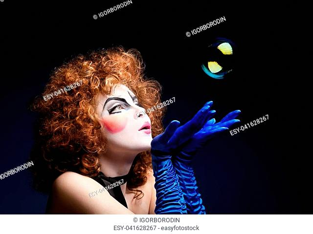 Woman mime with theatrical makeup and soap bubbles. Studio shot