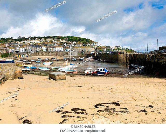 Mousehole harbour Cornwall England UK Cornish fishing village with blue sky and clouds