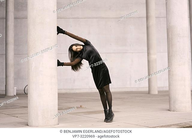 fashionable woman leaning head against pillars, architecture, in city Munich, Germany