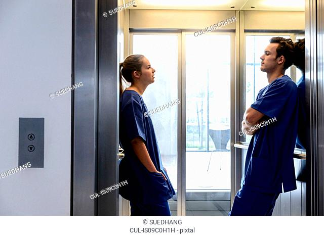 Young female and male junior doctors in hospital elevator