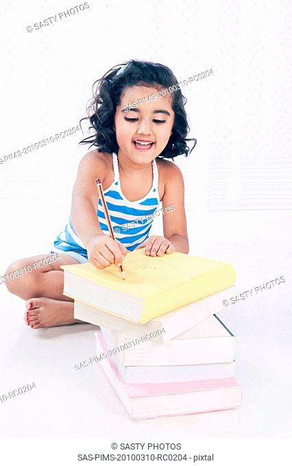 Girl writing on a book with a pencil