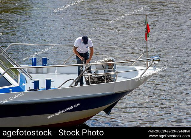 29 May 2020, Saxony-Anhalt, Magdeburg: A crew member of the MS Sachsen-Anhalt of the Magdeburg White Fleet catches up with the lines of the excursion ship