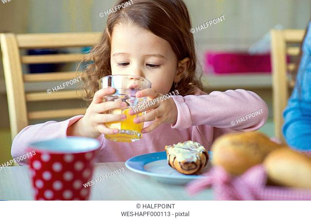 Portrait of little girl drinking glass of orange juice at breakfast table