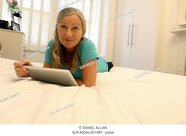 Older woman using tablet computer on bed