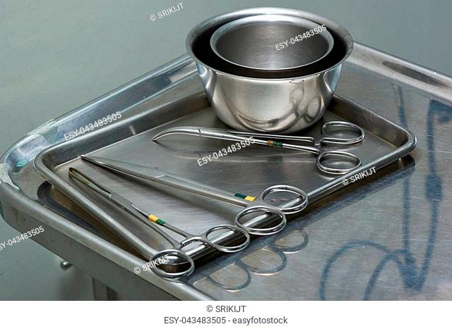 Used surgical instruments includings scissors, clamp, and cups on a stainless tray