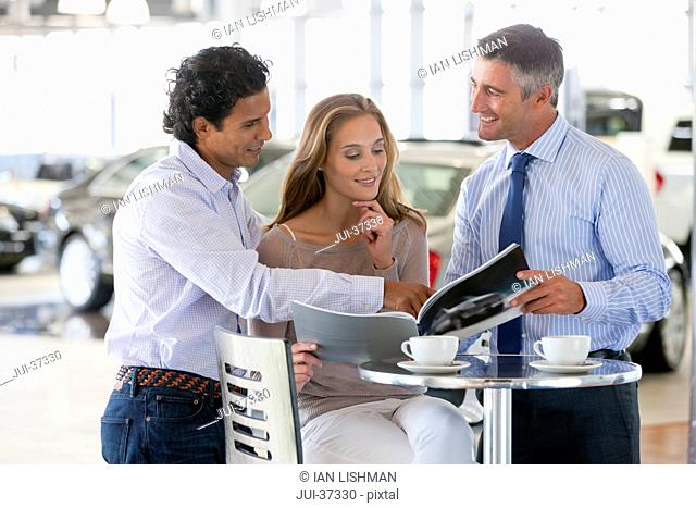 Salesman and couple looking at brochure at table in car dealership showroom