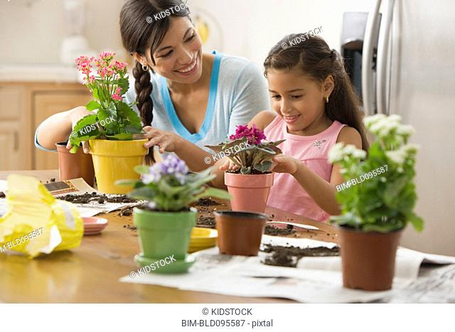 Mother and daughter planting flowers in pots