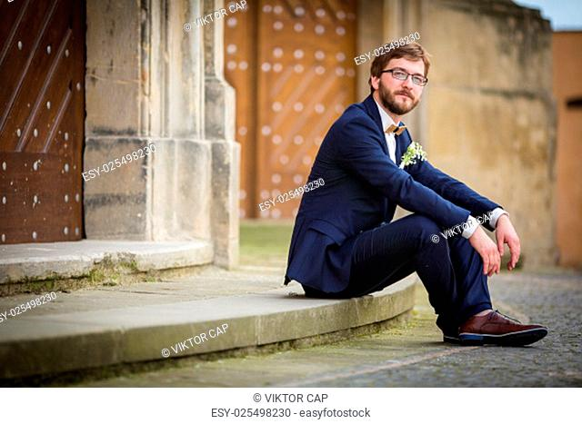 Handsome groom on his wedding day waiting for his bride in front of a church