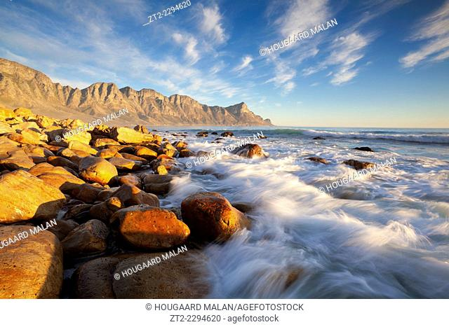 Landscape photo of a wave crashing against a rock. Kogelbay beach, Western Cape, South Africa