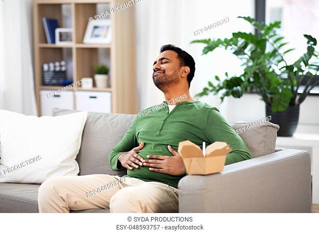 pleased indian man eating takeaway food at home