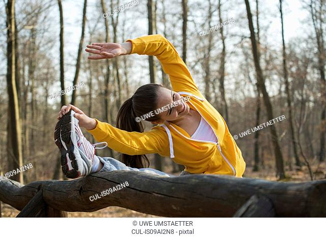 Young woman touching toes on assault course in forest