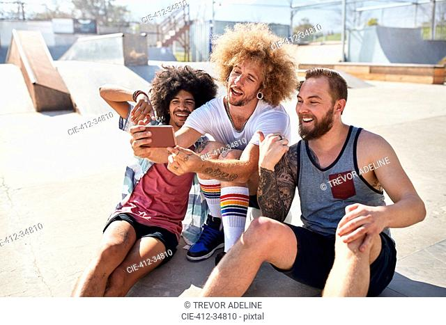 Male friends with camera phone taking selfie at sunny skate park