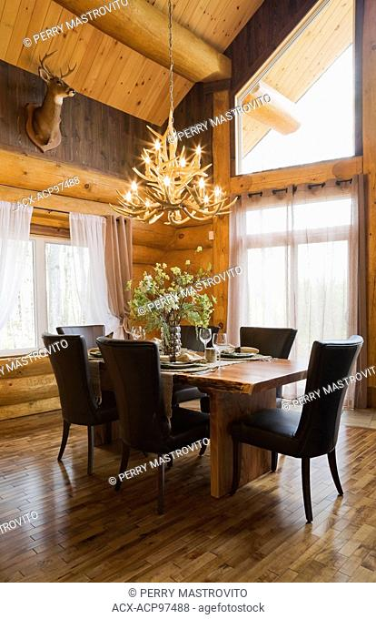 Natural wood dining table and brown leather chairs in the dining room inside a luxurious cottage style log home, Quebec, Canada