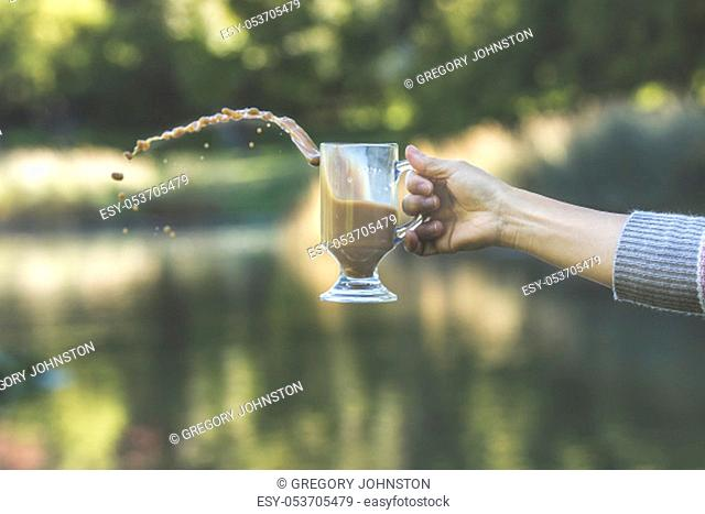 A conceptual photo of a person's hand causing a spill of the coffee from a glass mug