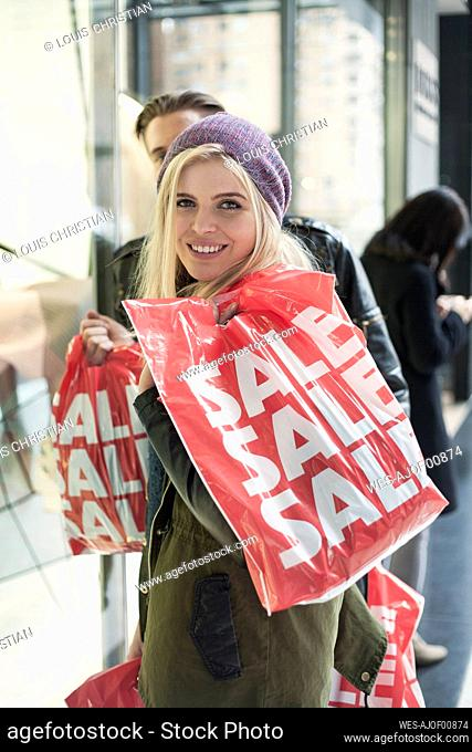 Woman holding shopping bag while standing with man by store window
