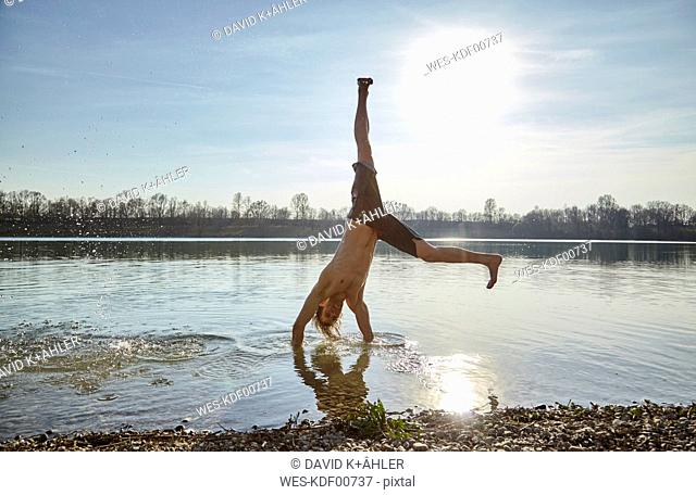 Germany, Bavaria, Feldkirchen, man turning wheels in lake