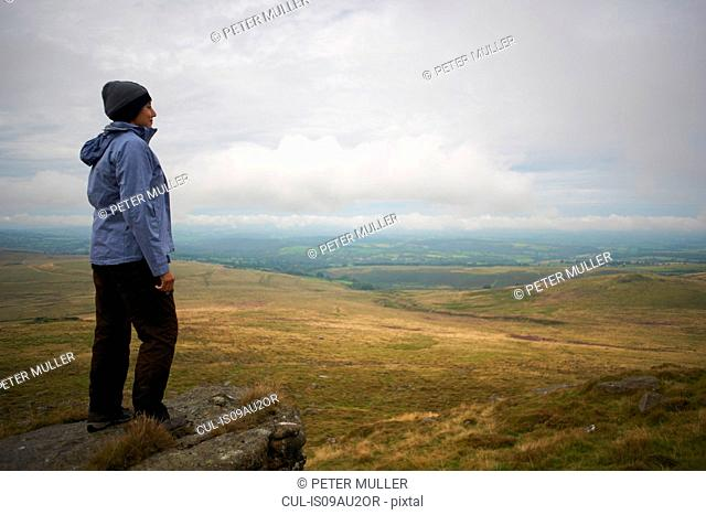 Woman enjoying view on rock formation, Dartmoor, Devon, UK