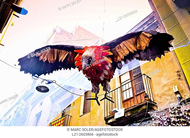 Sculpture of a bird hanging on a street with open wings. Handmade decorations by residents. Festa Major de Gracia. Gracia Summer Festival