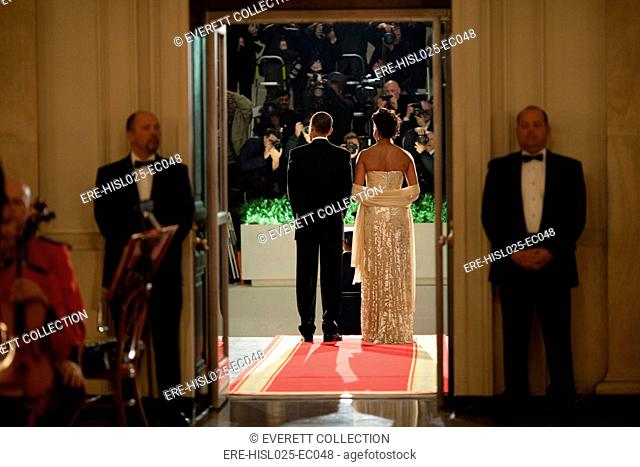 President and Michelle Obama face photographers as they await the arrival of Indian Prime Minister Manmohan Singh. Michelle's dress is adorned with hand cut...