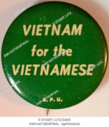 An anti-Vietnam War protest pin with a green background that features off-white lettering that reads 'Vietnam for the Vietnamese'