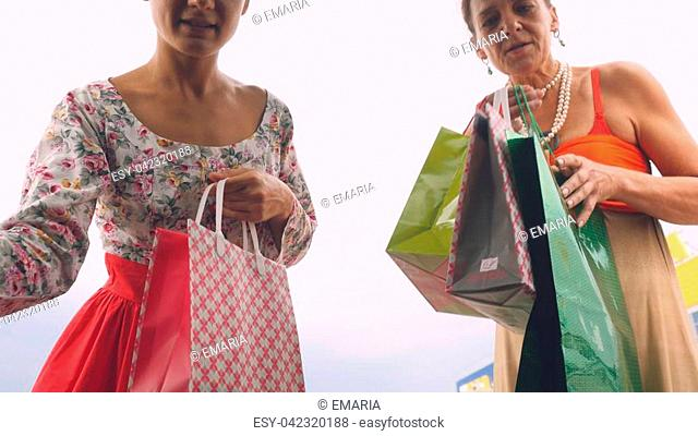 Happy women putting shopping bags into car trunk at shopping mall outdoor. Mum and her daughter have a shopping time