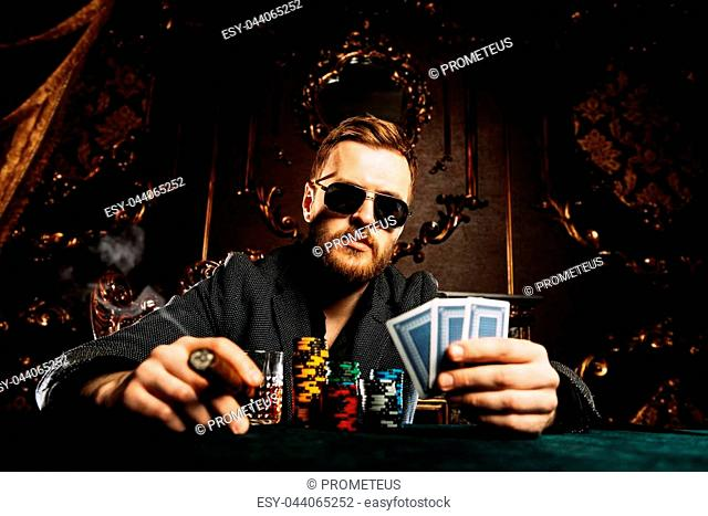 A wealthy mature man smoking cigar and playing poker in a casino. Gambling, playing cards and roulette
