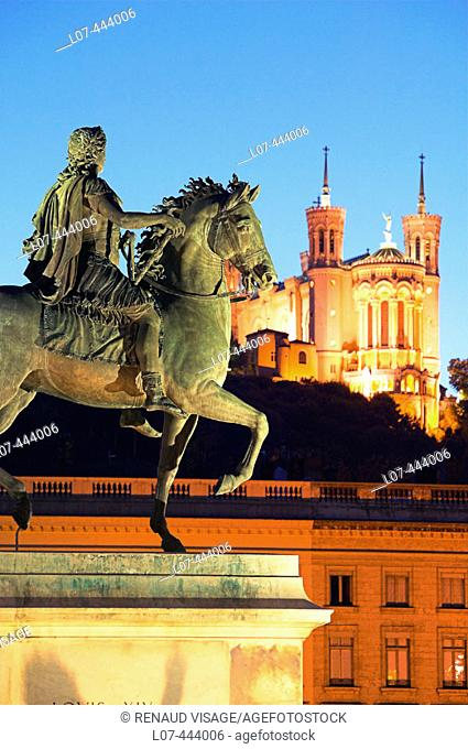 Equestrian statue of Louis XIV and church of Fourvière at dusk. Lyon. France
