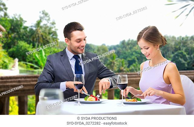 smiling couple eating appetizers at restaurant