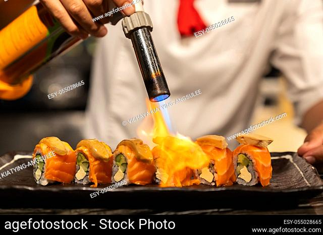 Chef cooking Salmon Foie gras roll, Fusion Japanese Cuisine food, using gas burner torch