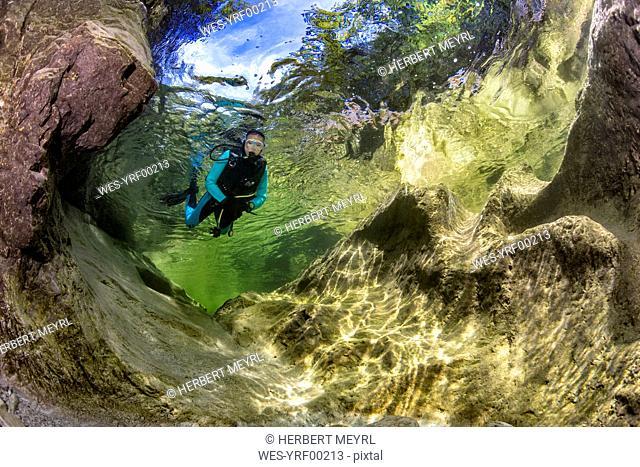Austria, Salzkammergut, river Weissenbach, female scuba diver in a wild mountain river