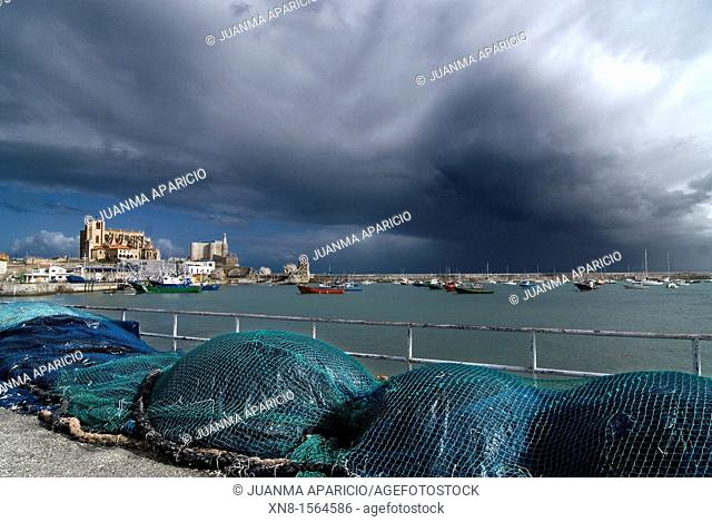 Horizontal image of Castro Urdiales with fishing gear in the foreground and a blue sky with spectacular clouds background, Cantabria, Spain
