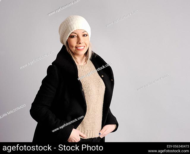 Pretty young woman poses with cheerful and friendly winter and fitness clothes