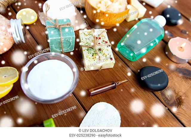 beauty, spa, therapy and wellness concept - natural bodycare cosmetics on wood over snow